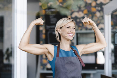 Proud busness owner flexing muscles, laughing - KNSF06321