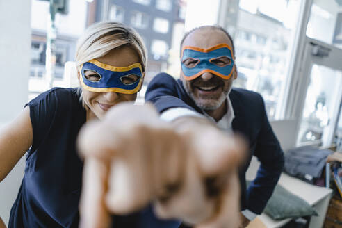Businessman and woman, wearing super hero masks, pointing at camera - KNSF06339