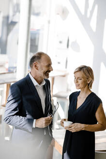 Businessman and woman talking about solutions, drinking coffee - KNSF06354