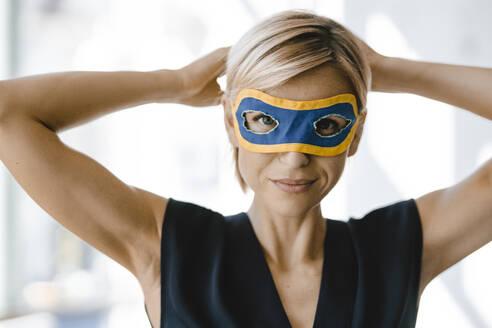 Portrait of blond businesswoman, wearing superwoman mask - KNSF06357