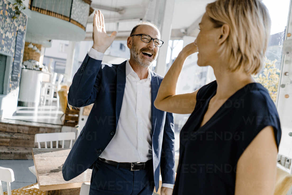 Business people high fiving in a coffee shop - KNSF06372 - Kniel Synnatzschke/Westend61
