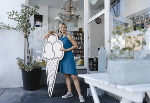 Woman standing in front of her coffee shop, holding icecream sign - KNSF06399