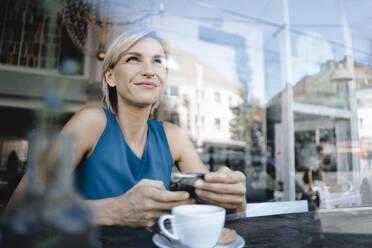 Businesswoman taking a break in coffee shop, holding smartphone - KNSF06402