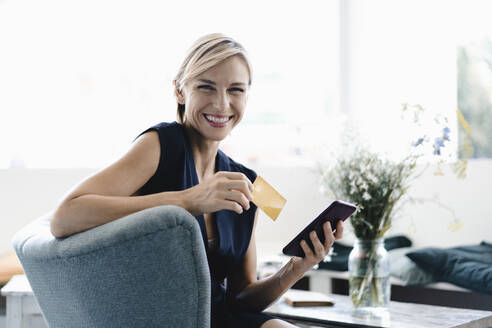 Businesswoman making online payment, using smartphone and credit card in a coffe shop - KNSF06420