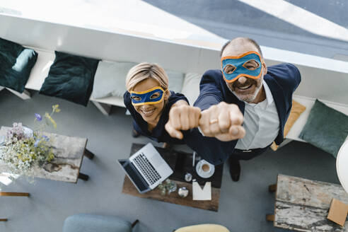 Businessman and woman wearing super hero masks, raising fists - KNSF06426
