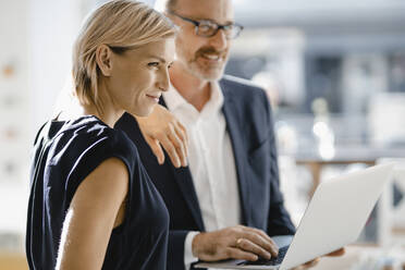 Businessman and woman standing in coffee shop, using laptop - KNSF06432