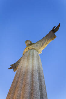 Low angle view of Christ the King statue against clear blue sky, Lisbon, Portugal - XCF00197