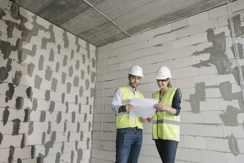 Two architects talking while standing at construction site - AHSF00804