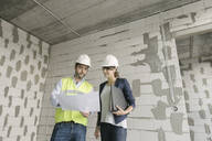 Two architects checking architectural plan while standing at construction site - AHSF00807