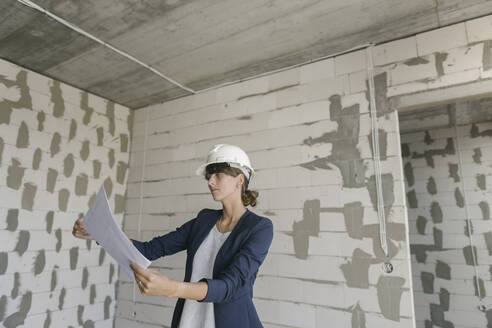 Female architect checking architectural plan on construction site - AHSF00813
