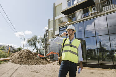 Architect using phone on construction site - AHSF00819