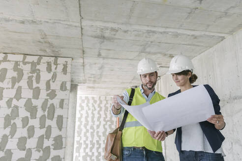 Architect and female manager talking about architectural plan at construction site - AHSF00822