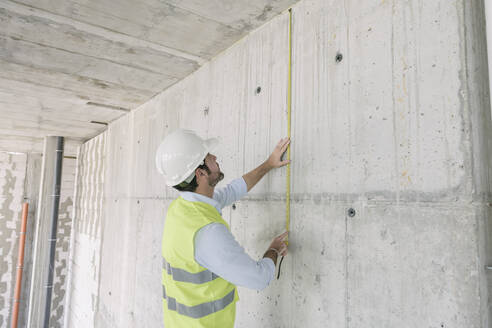 Architect metering a wall at construction site - AHSF00828