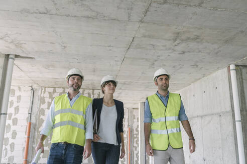 Male architects and female manager walking at construction site - AHSF00831