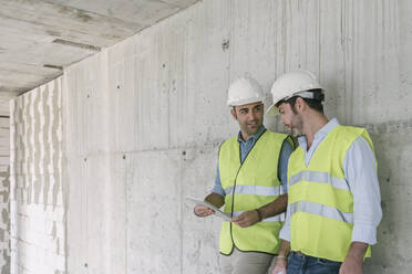 Two workers using tablet on construction site - AHSF00834