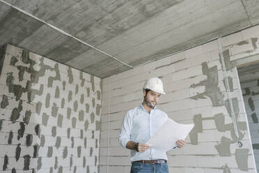 Architect checking architectural plan on construction site - AHSF00837
