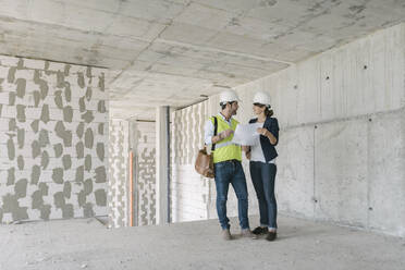 Male architect and female manager talking at construction site - AHSF00843