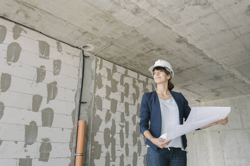 Female architect checking architectural plan on construction site - AHSF00846