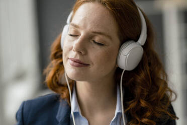 Portrait of redheaded businesswoman listening music with white headphones - KNSF06437