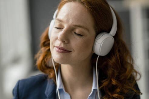 Portrait of redheaded businesswoman listening music with white headphones - KNSF06437