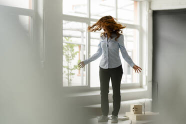 Redheaded woman standing on desk in a loft moving and screaming - KNSF06449