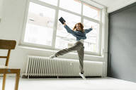 Portrait of redheaded woman with digital tablet jumping in the air in a loft - KNSF06467