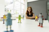 Portrait of redheaded businesswoman in a loft with miniature robots on desk - KNSF06476