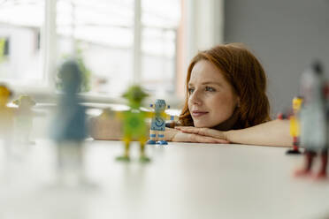Portrait of redheaded businesswoman in a loft with miniature robots on desk - KNSF06479