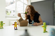 Portrait of redheaded businesswoman in a loft with miniature robots on desk eating healthy takeaway food - KNSF06485
