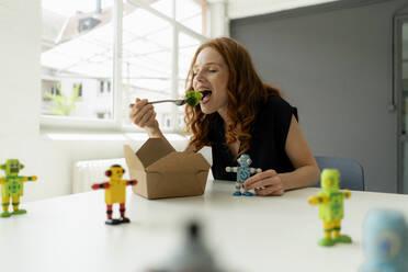 Portrait of redheaded businesswoman in a loft with miniature robots on desk eating healthy takeaway food - KNSF06485