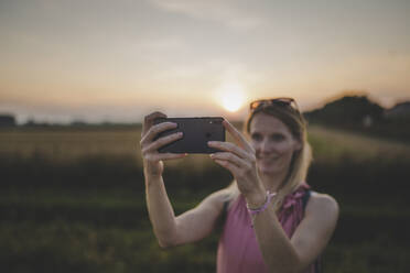 Woman taking a selfie at sunset - CHPF00574