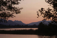 Scenic view of Forggensee lake and silhouette mountains against clear sky during sunset at Ostallgäu, Germany - JTF01298
