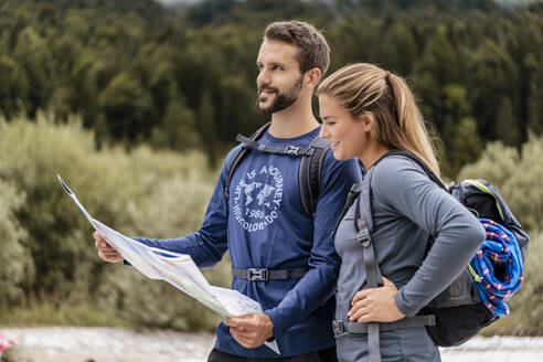 Young couple on a hiking trip reading map, Vorderriss, Bavaria, Germany - DIGF08259