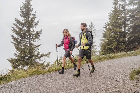 Young couple on a hiking trip in the mountains, Herzogstand, Bavaria, Germany - DIGF08262