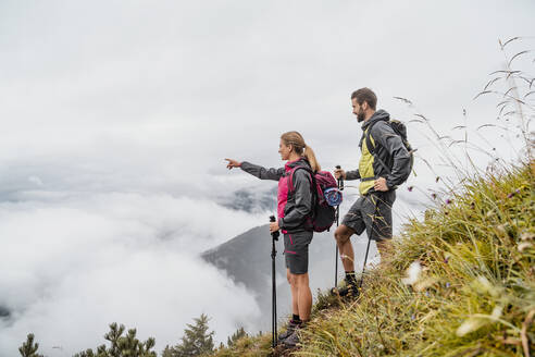 Young couple on a hiking trip in the mountains looking at view, Herzogstand, Bavaria, Germany - DIGF08268