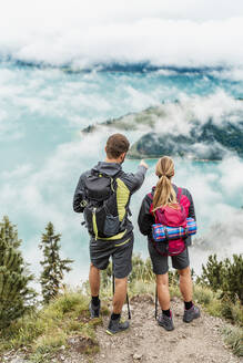 Young couple on a hiking trip in the mountains looking at view, Herzogstand, Bavaria, Germany - DIGF08271