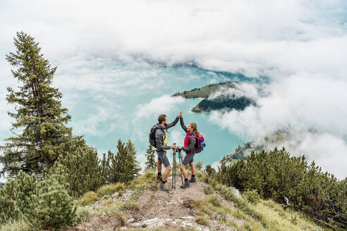 Happy young couple on a hiking trip in the mountains high fiving, Herzogstand, Bavaria, Germany - DIGF08274