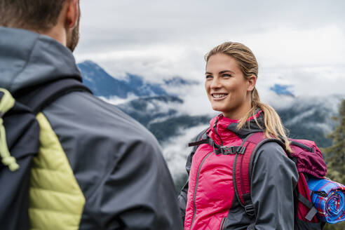 Smiling young couple on a hiking trip in the mountains, Herzogstand, Bavaria, Germany - DIGF08277