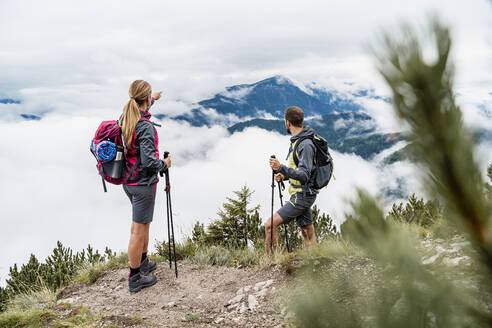 Young couple on a hiking trip in the mountains looking at view, Herzogstand, Bavaria, Germany - DIGF08280