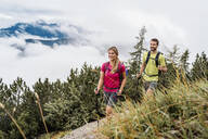 Confident young couple on a hiking trip in the mountains, Herzogstand, Bavaria, Germany - DIGF08283