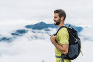 Smiling young man on a hiking trip in the mountains looking at view, Herzogstand, Bavaria, Germany - DIGF08295