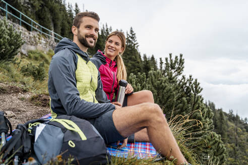 Young couple on a hiking trip in the mountains having a break, Herzogstand, Bavaria, Germany - DIGF08301