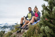 Young couple on a hiking trip in the mountains having a break, Herzogstand, Bavaria, Germany - DIGF08304