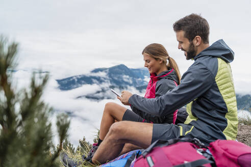 Young couple on a hiking trip in the mountains having a break using cell phone, Herzogstand, Bavaria, Germany - DIGF08307