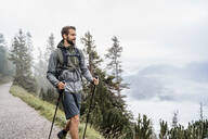 Young man on a hiking trip in the mountains, Herzogstand, Bavaria, Germany - DIGF08310