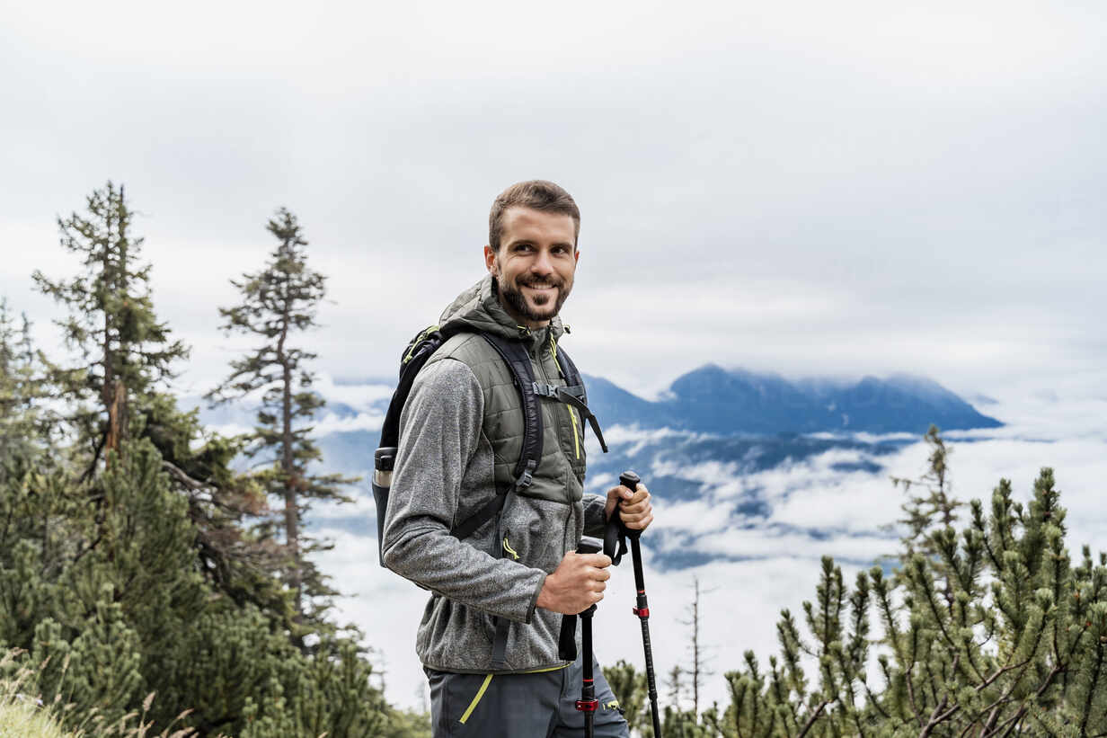 Smiling young man on a hiking trip in the mountains, Herzogstand, Bavaria, Germany - DIGF08313 - Daniel Ingold/Westend61