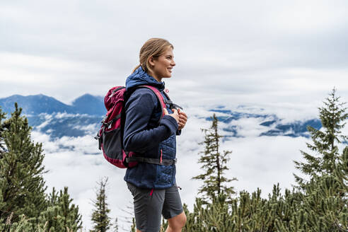 Smiling young woman on a hiking trip in the mountains, Herzogstand, Bavaria, Germany - DIGF08316