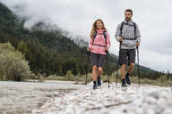 Young couple on a hiking trip at riverside, Vorderriss, Bavaria, Germany - DIGF08331