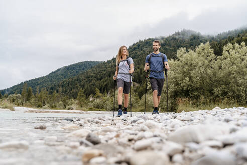 Young couple on a hiking trip at riverside, Vorderriss, Bavaria, Germany - DIGF08337