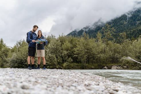 Young couple on a hiking trip at riverside reading map, Vorderriss, Bavaria, Germany - DIGF08340